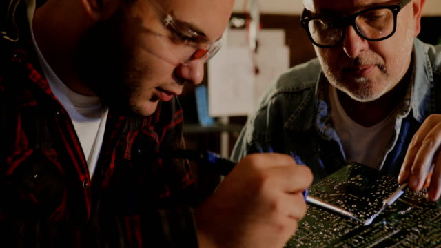 two male engineer trying to fix electric circuit by soldering it... - riparare video stock e b–roll
