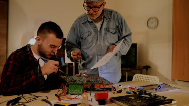 two male engineer trying to fix electric circuit by soldering it... - scientific experiment stock videos & royalty-free footage