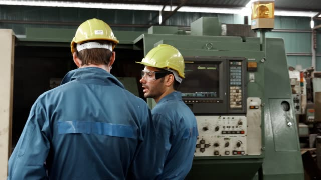 two male engineers inspecting the industrial machinery in operation in the factory - employee stock videos & royalty-free footage