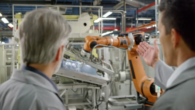 Two male engineers inspecting the industrial robots in operation in the factory