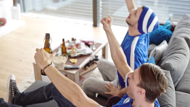 Two male friends celebrating the score in front of TV
