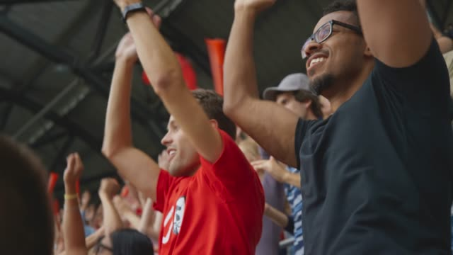 Two male friends cheering on the stadium tribune at a football match
