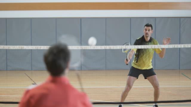 vídeos de stock, filmes e b-roll de dois amigos homens jogando badminton indoor - badmínton esporte