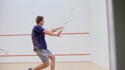 Two male friends playing squash