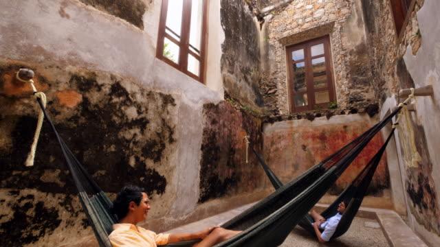 TD Two male friends relaxing in hammocks at luxury resort