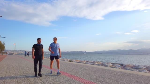 vídeos de stock e filmes b-roll de two male friends walking at seaside - andar depressa