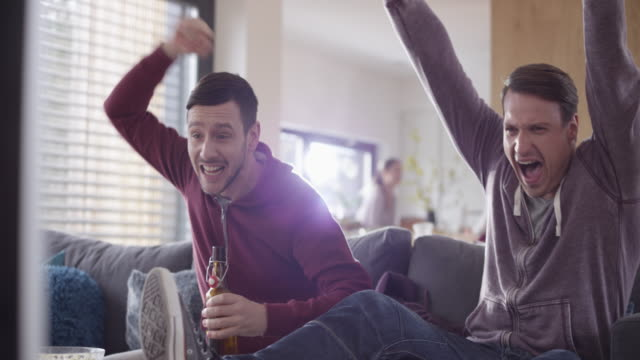 two male friends watching football match and celebrating a goal - watching tv stock videos & royalty-free footage