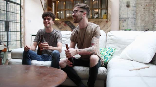 Two male friends watching sport