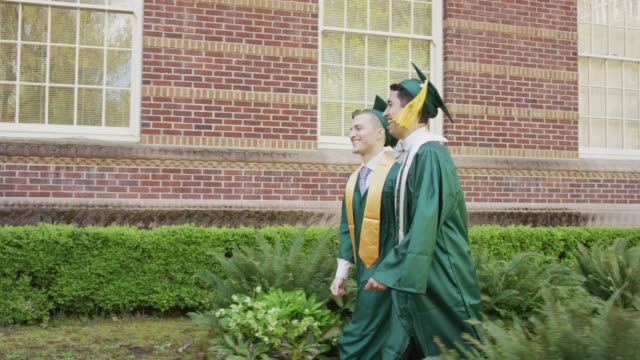 vídeos de stock e filmes b-roll de two male graduates holding hands and walking - 20 24 anos