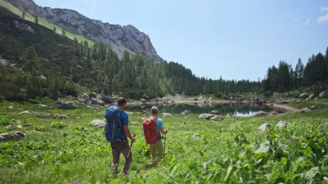 Two male hikers walking towards a mountain lake in sunshine