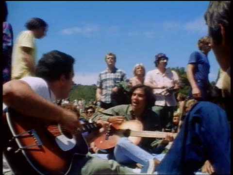1968 two male hippies sitting on ground playing acoustic guitars outdoors / tapia park ca - peace demonstration stock videos and b-roll footage