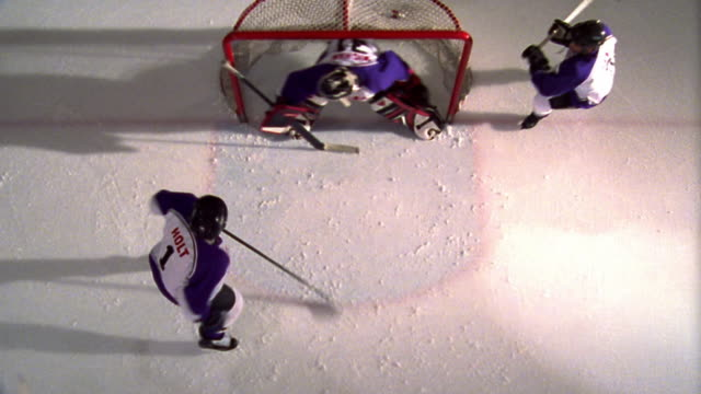 OVERHEAD two male ice hockey teams playing near net / yellow team scoring goal + celebrating