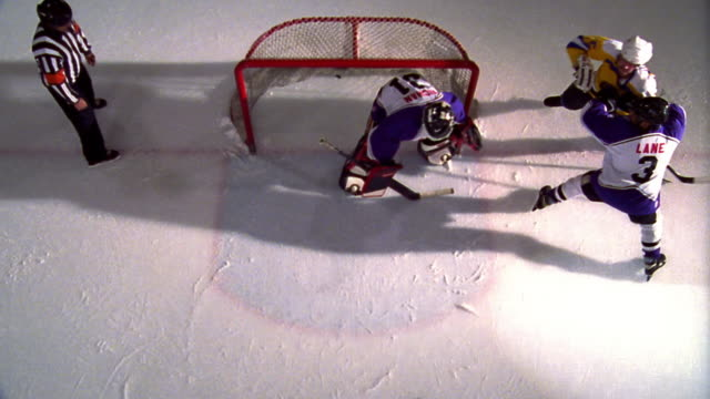 vídeos de stock, filmes e b-roll de overhead two male ice hockey teams playing near net / yellow team scoring goal + celebrating - árbitro