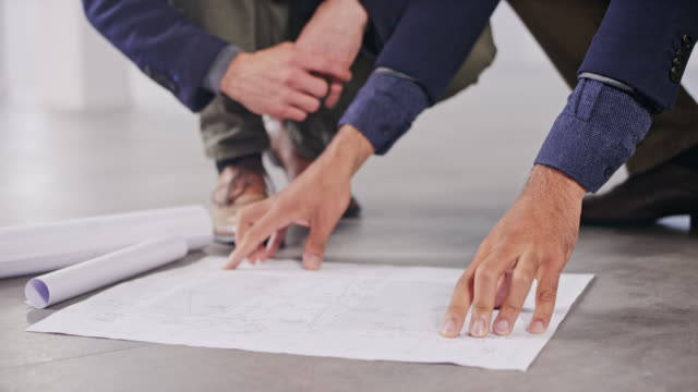 ds two male interior architects pointing on details on the plan set on the floor of an empty office space and discussing them - architect stock videos & royalty-free footage