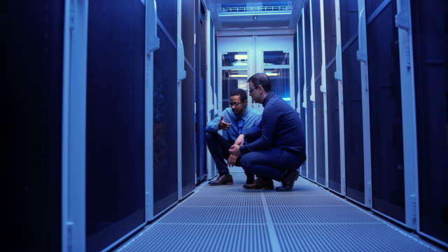 Two male IT technicians crouching by the servers in the server room and checking the operations