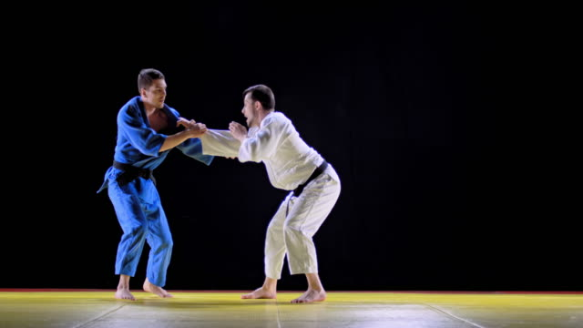 slo mo two male judo contestants doing the standing bow and starting the fight - world sports championship stock videos & royalty-free footage