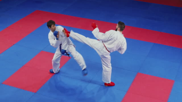two male karate competitors fighting on the tatami - combat sport stock videos & royalty-free footage