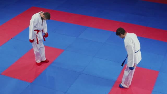 zwei männliche karate starten den kampf auf dem tatami mit einem bogen - asiatischer kampfsport stock-videos und b-roll-filmmaterial