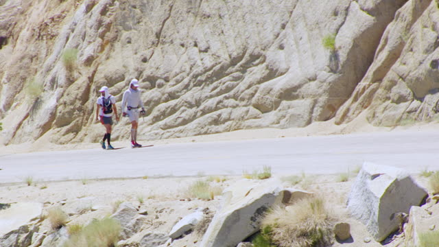 MS TU AERIAL POV Two male marathoners walking on Whitney Portal Road / California, United States