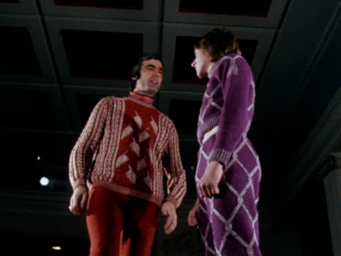 stockvideo's en b-roll-footage met two male models stand on the catwalk wearing tight brightly coloured and patterned woollen jumpers and trousers. 1970. - herenkleding