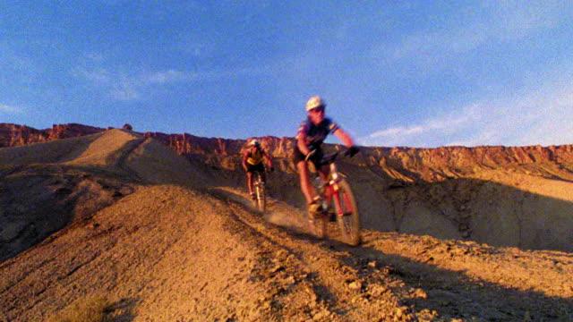 vidéos et rushes de two male mountain bikers riding toward + past camera on dirt ridge in desert / western colorado - aride