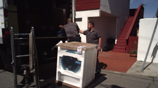 ms two male movers unload washing machine from truck and carring up exterior house /  manhattan beach,california,united states - 家電製品点の映像素材/bロール