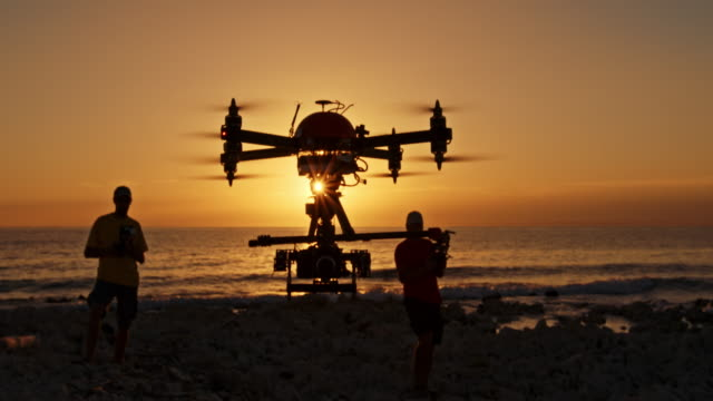 two male operators controlling drone at sunset - in silhouette stock videos & royalty-free footage