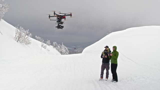 Two male operators flying a drone in snowy landscape