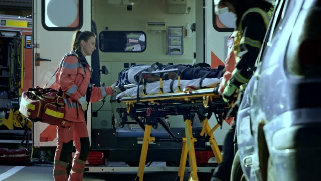 two male paramedics loading the injured person into the ambulance and the female doctor accompanies the patient - stretcher stock videos & royalty-free footage