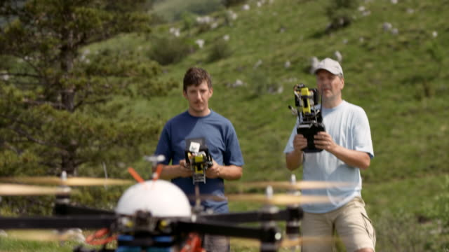 Two male pilots taking the drone off the ground