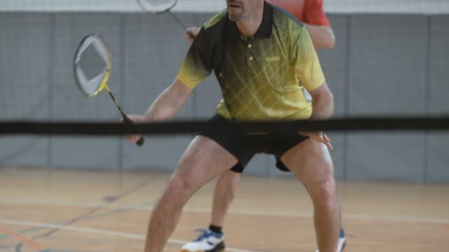 vídeos de stock, filmes e b-roll de dois jogadores do sexo masculino jogando duplas no badminton indoor - badmínton esporte