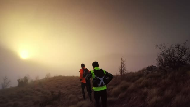 two male runner running across a mountain towards the sun rising behind the fog - two people stock videos & royalty-free footage
