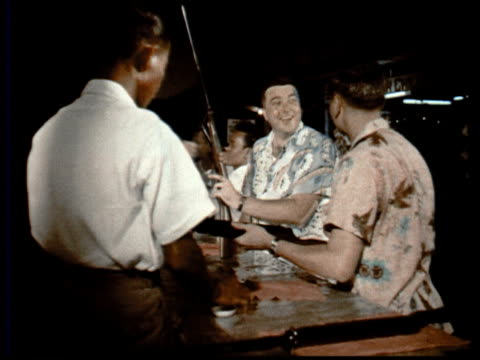 1957 montage two male tourists at amusement park shooting gallery w/ rifles / singapore / audio - shooting range stock videos and b-roll footage