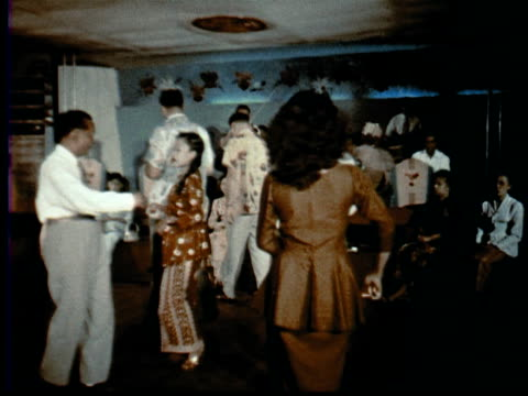 1957 montage two male tourists in malay dance hall doing ronggeng / singapore / audio - 1957 bildbanksvideor och videomaterial från bakom kulisserna