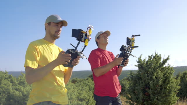Two male UAV operators holding the remote controllers