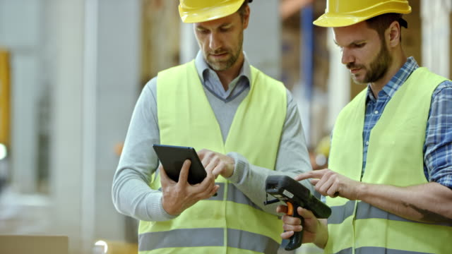 Two male warehouse supervisors comparing inventory data on the scanner and digital tablet