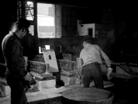 vidéos et rushes de two male workers in heat protective gloves goggles one working w/ long handle container lifting scoop out containment area below floor possibly... - 1952