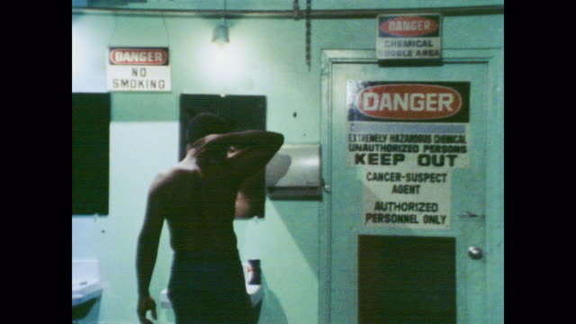 vidéos et rushes de 1978 two male workers preen in changing room with cancer warning signs - homme sous la douche