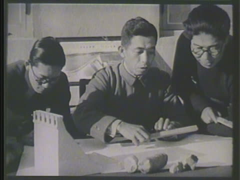 two males in coats looking over plans standing on scaffolding construction scene bg int ms japanese engineers looking over plans vs chinese laborers... - 満州地方点の映像素材/bロール