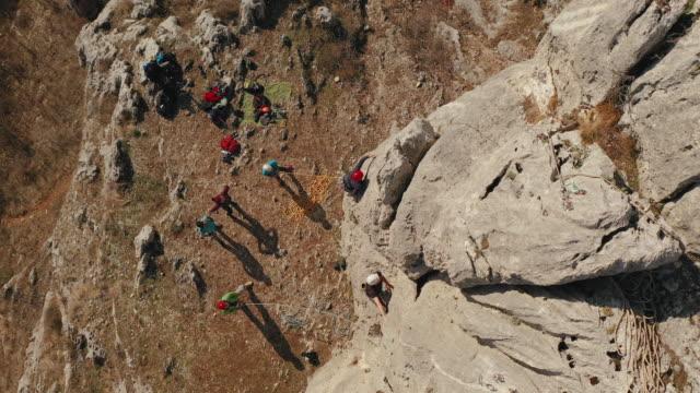 zwei männer klettern mit einem seil auf einen felsen. sportklettern, blei. - outdoor pursuit stock-videos und b-roll-filmmaterial