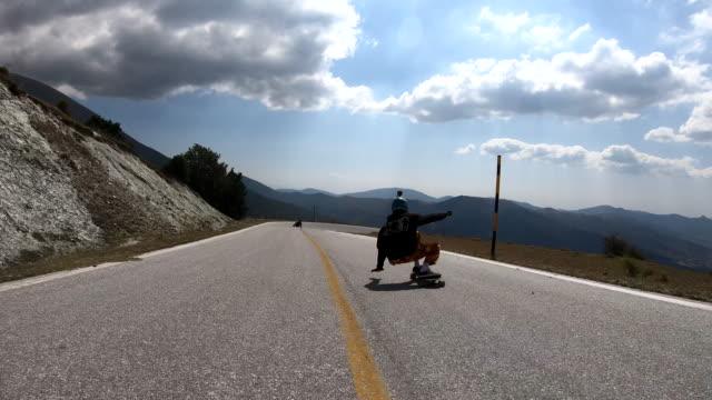 two man driving longboard down the mountain - longboarding stock videos & royalty-free footage