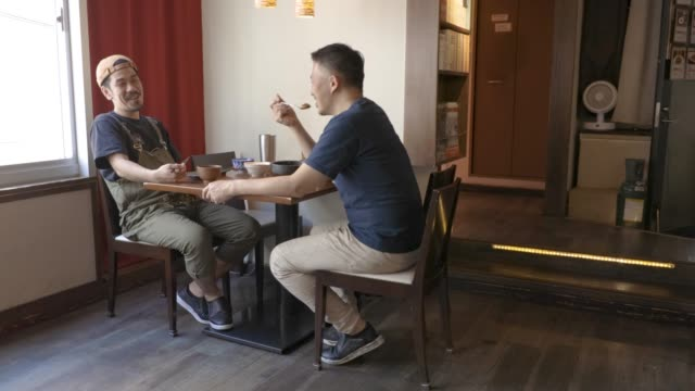 two man having conversation while eating lunch at izakaya, japnese pub - lunch break stock videos & royalty-free footage