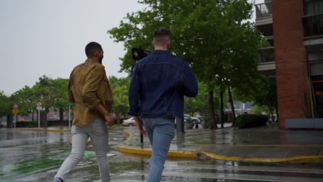 雨が降りながら手をつないで歩く二人の男 - ゲイ点の映像素材/bロール