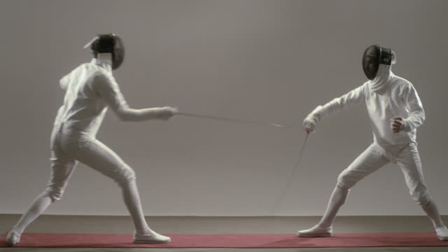 WS Two man in fencing gear raising foils and beginning match/ New York, New York
