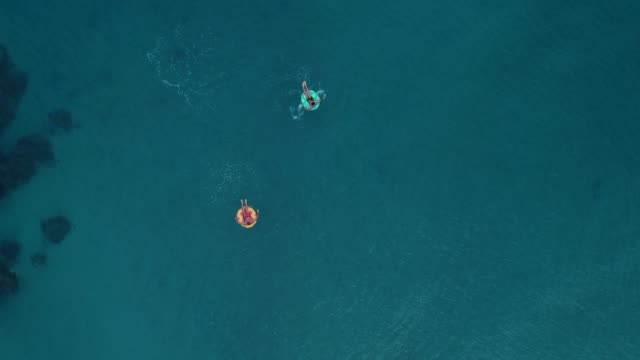 two man relaxing on inflatable rings - inflatable stock videos and b-roll footage