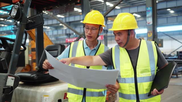 two man technicians in yellow helmet discuss project in steel sheet workshop - pensionati lavoratori video stock e b–roll