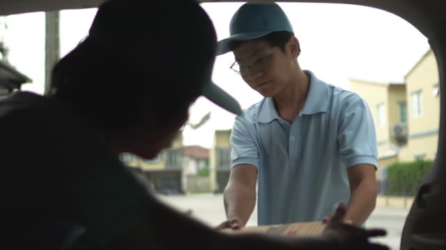 vídeos de stock, filmes e b-roll de dois homens descarregando o porta-malas do carro com caixas de papelão (desapareça) - fade out