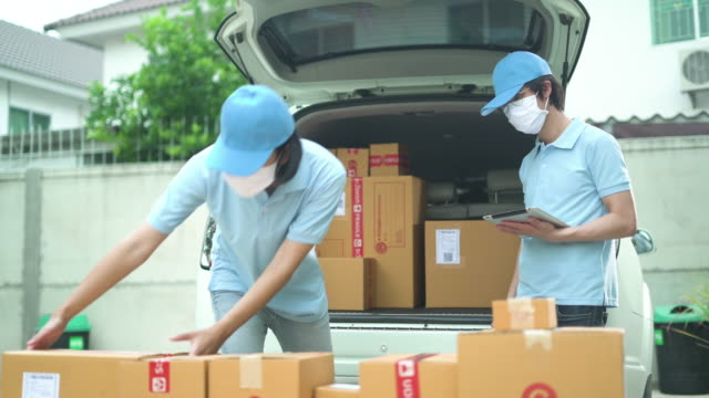 two man wear mask loading the car trunk with cardboard boxes - south east asia stock videos & royalty-free footage
