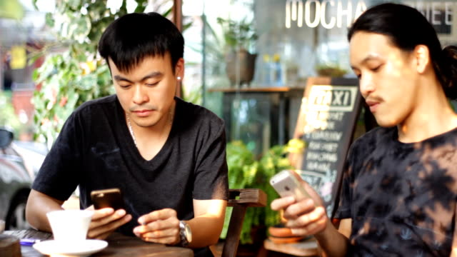 two mans smoking and talking while using smart phone and drink coffee - coffee drink stock videos & royalty-free footage