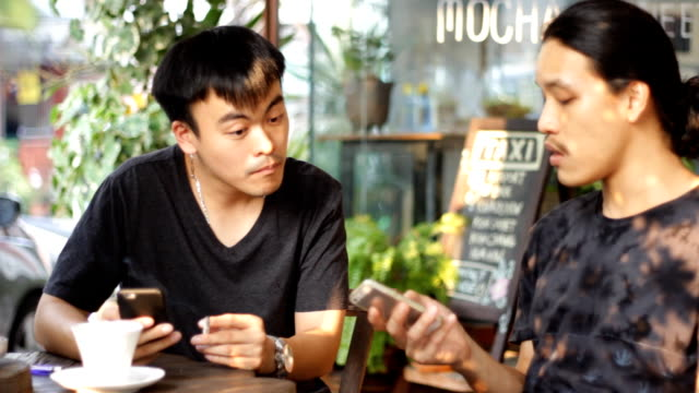 two mans smoking and talking while using smart phone and drink coffee